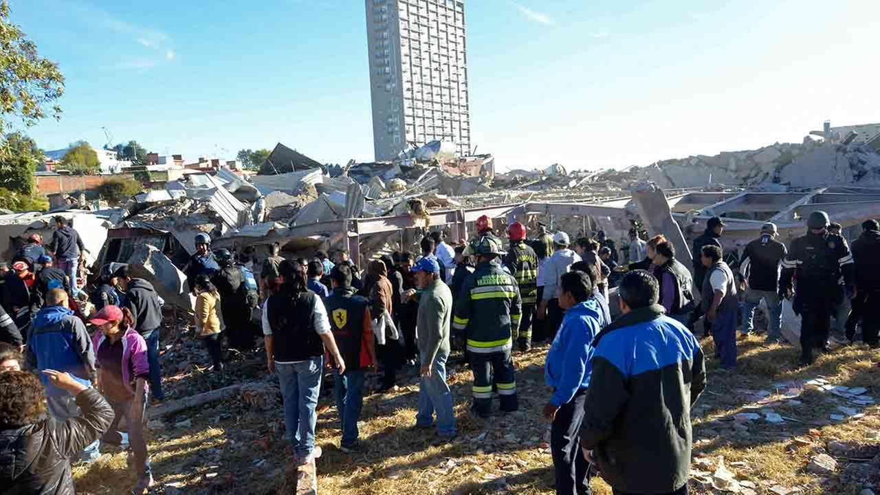 Rescue workers stand before the rubble of a childrens hospital where a gas truck exploded, in Cuajimalpa on the outskirts of Mexico City, Thursday, Jan. 29, 2015.