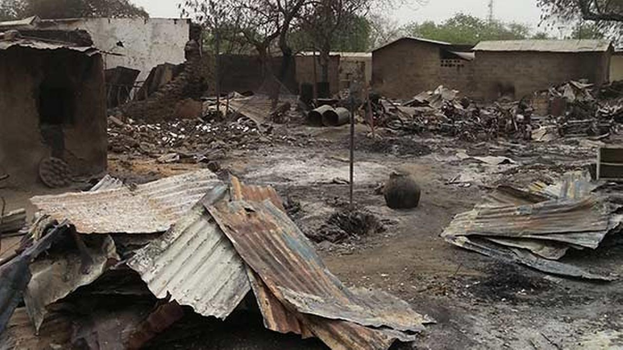 In this file photo taken with a mobile phone, the ruins of burnt out houses stand in Baga village in Nigeria.