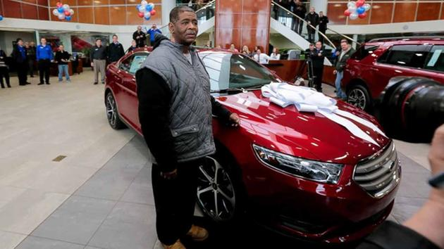 James Robertson, 56, of Detroit stands next to his free 2015 Ford Taurus from Suburban Ford in Sterling Heights on Friday, Feb. 6, 2015.