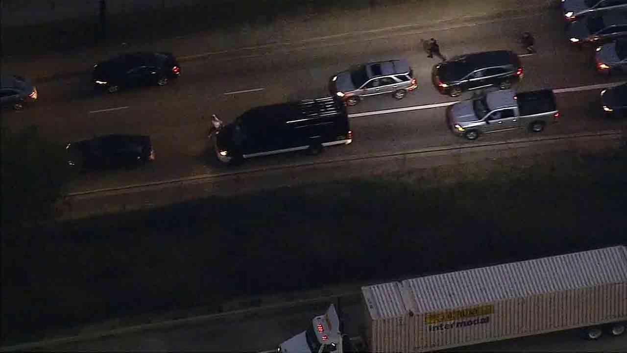 Los Angeles police officers chase after a stolen vehicle suspect who tried to carjack a motorist on the 60 Freeway in Montebello Monday, Feb. 9, 2015.