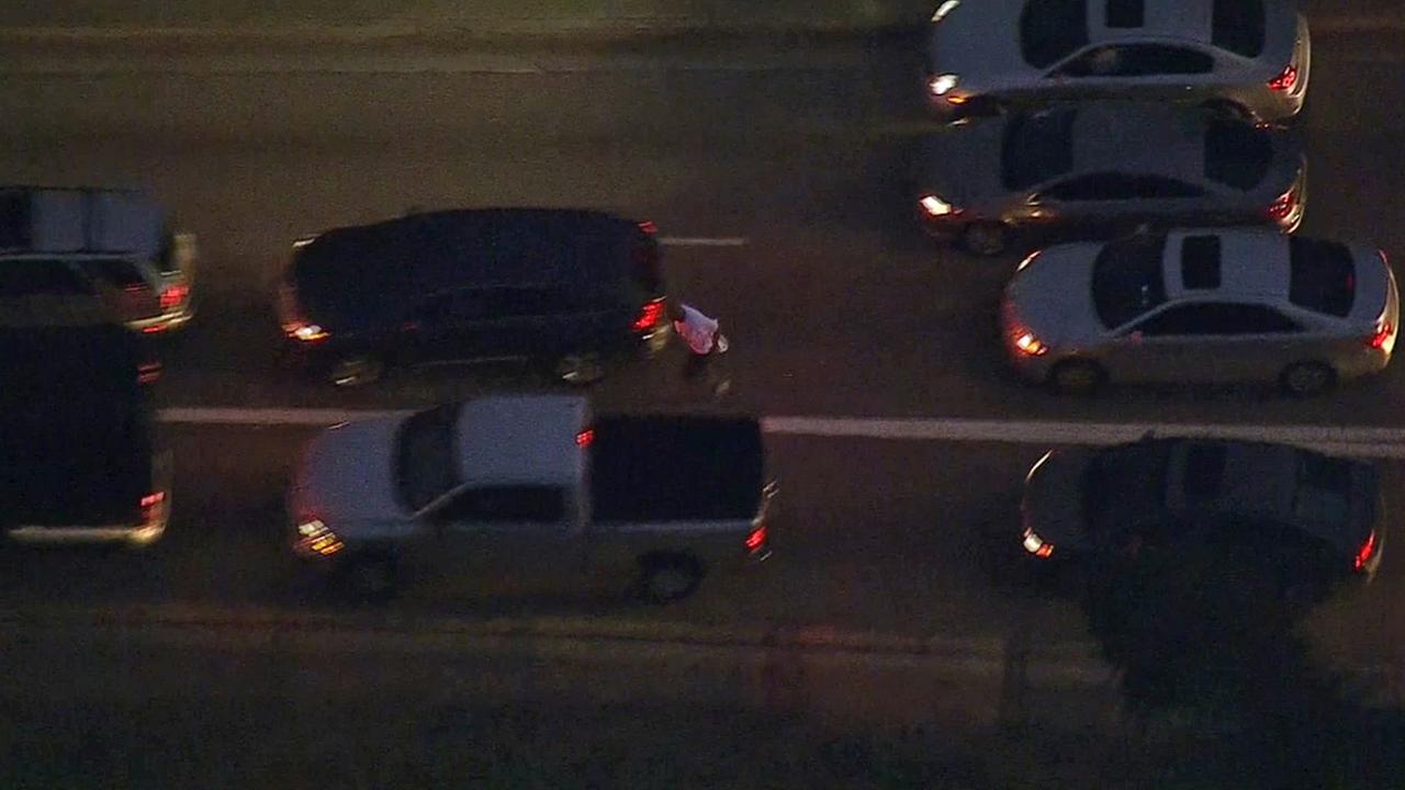 A man, who led police on a wild car chase through Montebello, flees from his stolen vehicle after getting stuck between two cars in traffic on the 60 Freeway on Monday, Feb. 9, 2015.