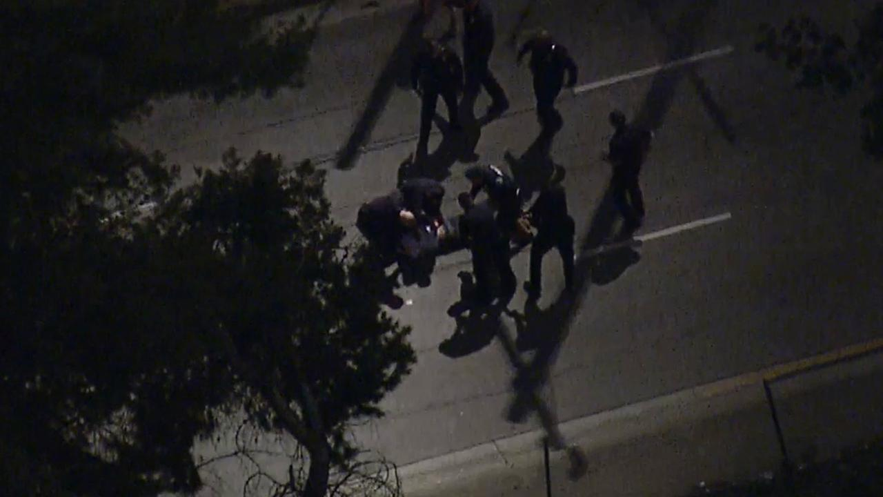Several LAPD officers surround and handcuff a suspect that led officers on a high-speed chase on Monday, Feb. 9, 2015.