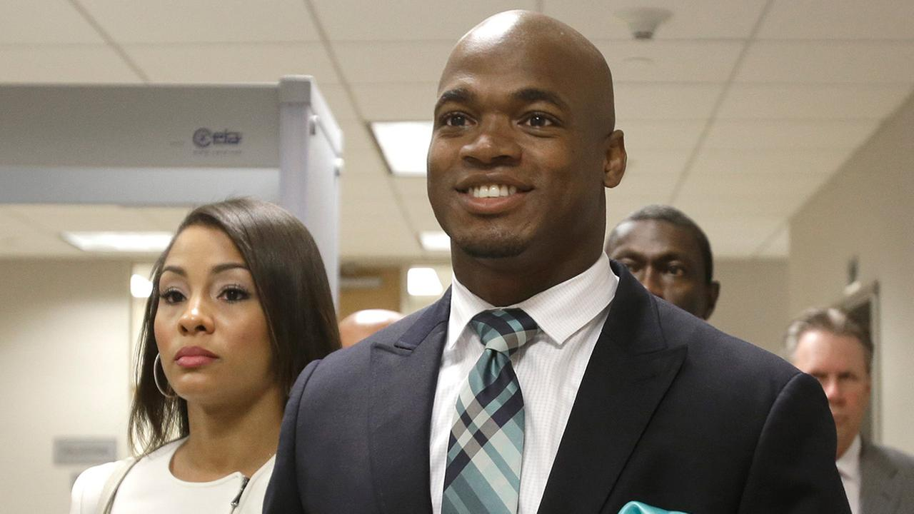 In this Nov. 4, 2014, file photo, Minnesota Vikings running back Adrian Peterson leaves the courthouse with his wife Ashley Brown Peterson in Conroe, Texas.