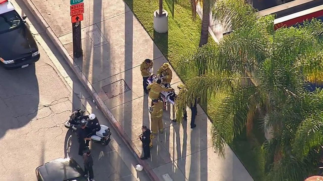 Los Angeles firefighters treat a Department of Transportation officer who was reportedly struck by a car on Wednesday, March 4, 2015.