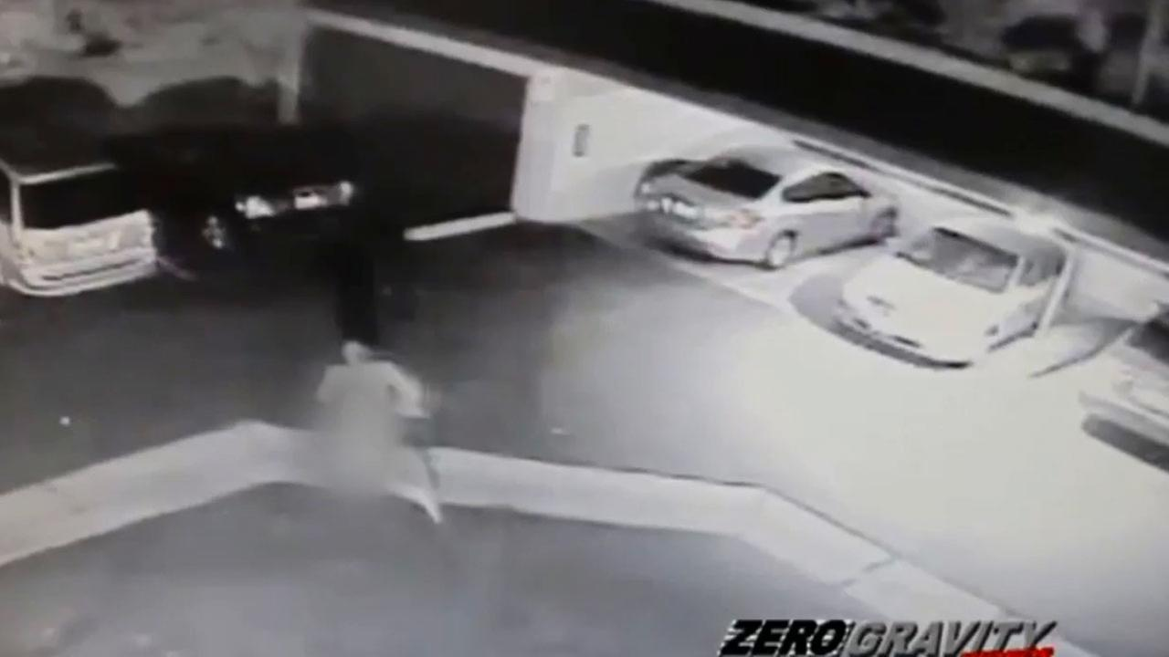 A surveillance camera captured a naked man smashing the back window of a parked van and jumping onto the hood of a moving car in Anaheim Saturday, March 7, 2015.