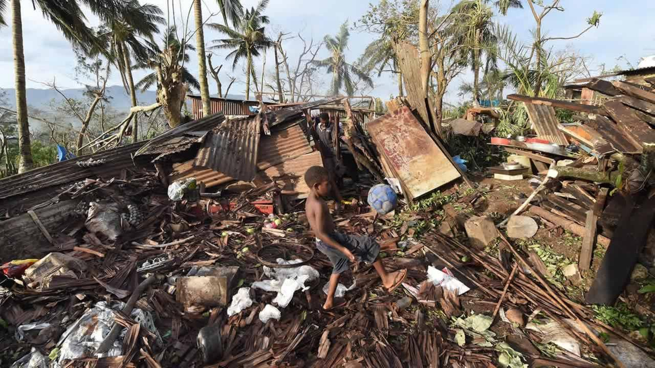 Samuel carries a ball through the ruins of their family home as his father, Phillip, at back, picks through the debris in Port Vila, Vanuatu after Cyclone Pam on March 16, 2015.
