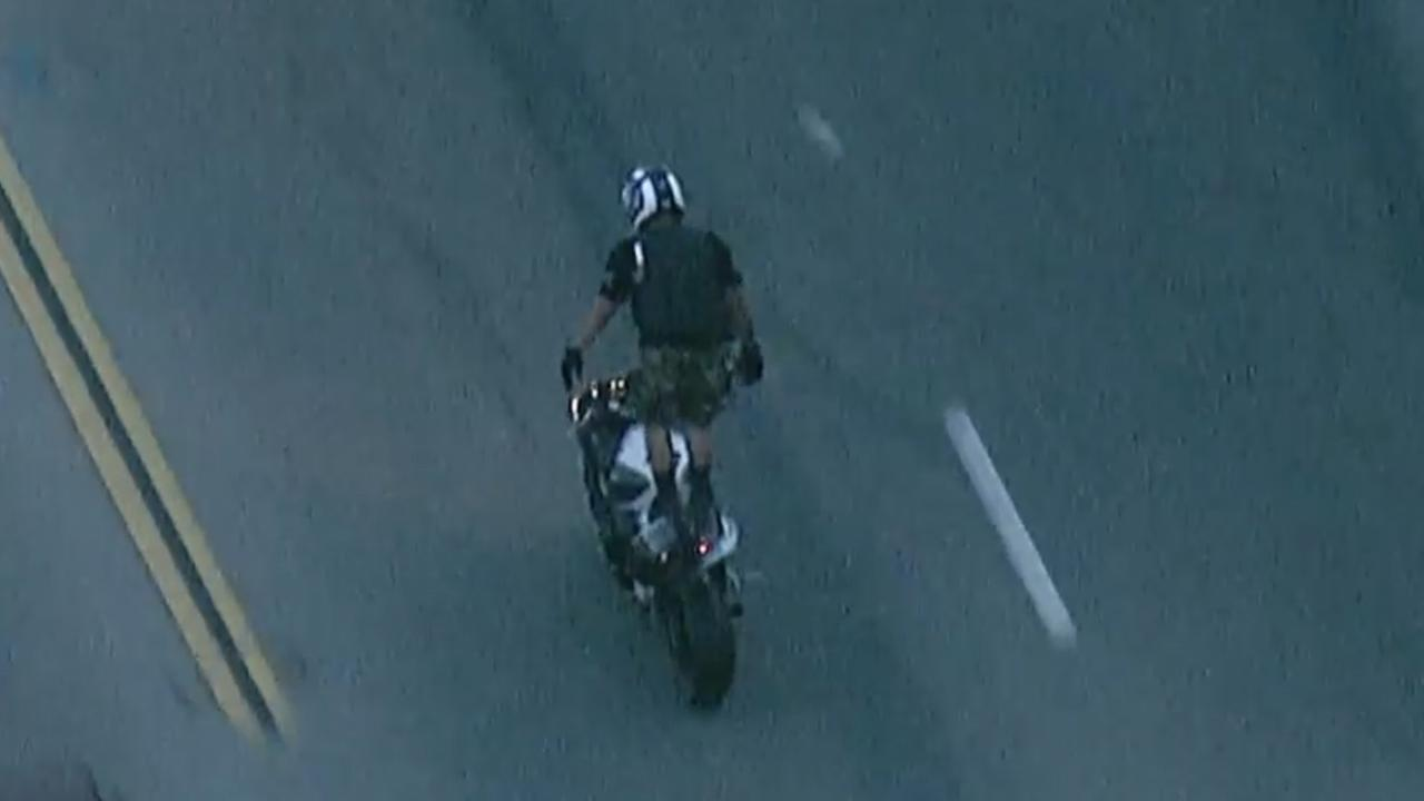 A motorcyclist stands up on his bike during a high-speed pursuit on Wednesday, March 18, 2015.