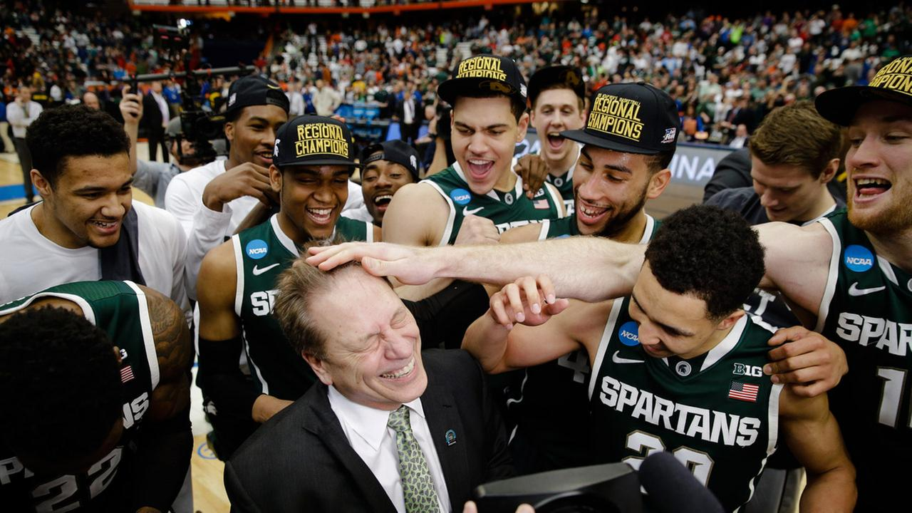 Michigan State head coach Tom Izzo celebrates with his team after the regional final against Louisville in the NCAA mens college basketball tournament Sunday, March 29, 2015.
