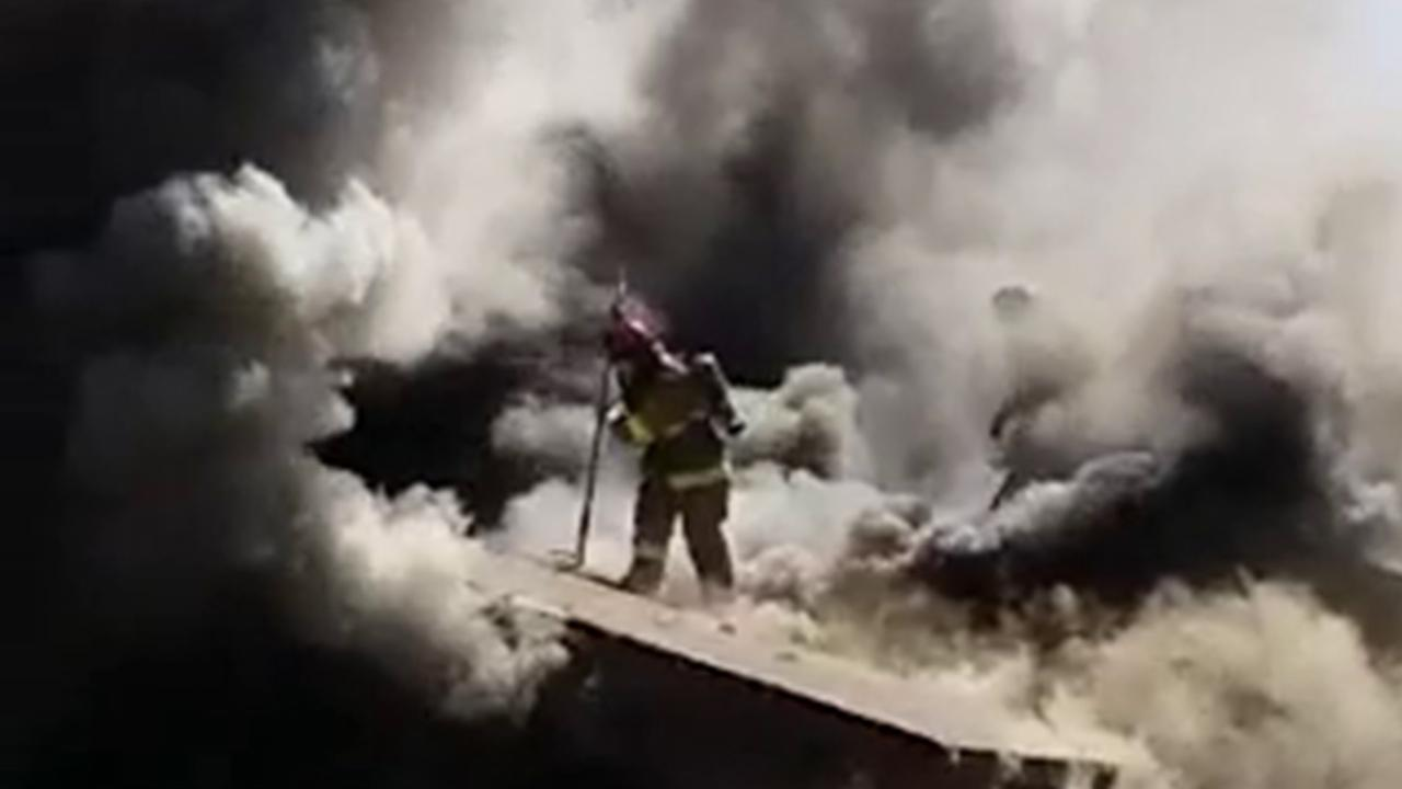 A Fresno firefighter is caught on camera falling through a roof into a burning home on Sunday, March 29, 2015.