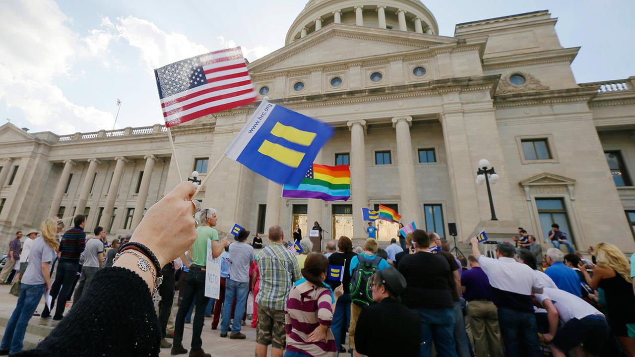 Demonstrators wave flags as they attend a rally at the Arkansas state Capitol in Little Rock, Ark., Tuesday, March 31, 2015, in protest of a bill passed by the state House critics say will lead to discrimination against gays and lesbians.