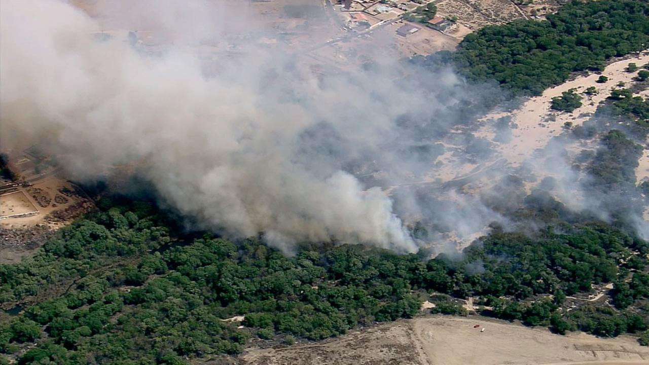 A brush fire burns near homes in the Spring Valley Lake community on Tuesday, March 31, 2015.