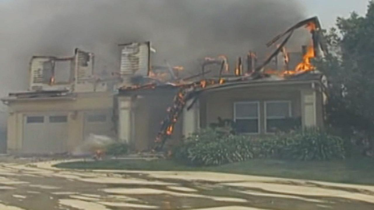 A house is damaged by flames from a brush fire in Carlsbad, California, on Wednesday, May 14, 2014.