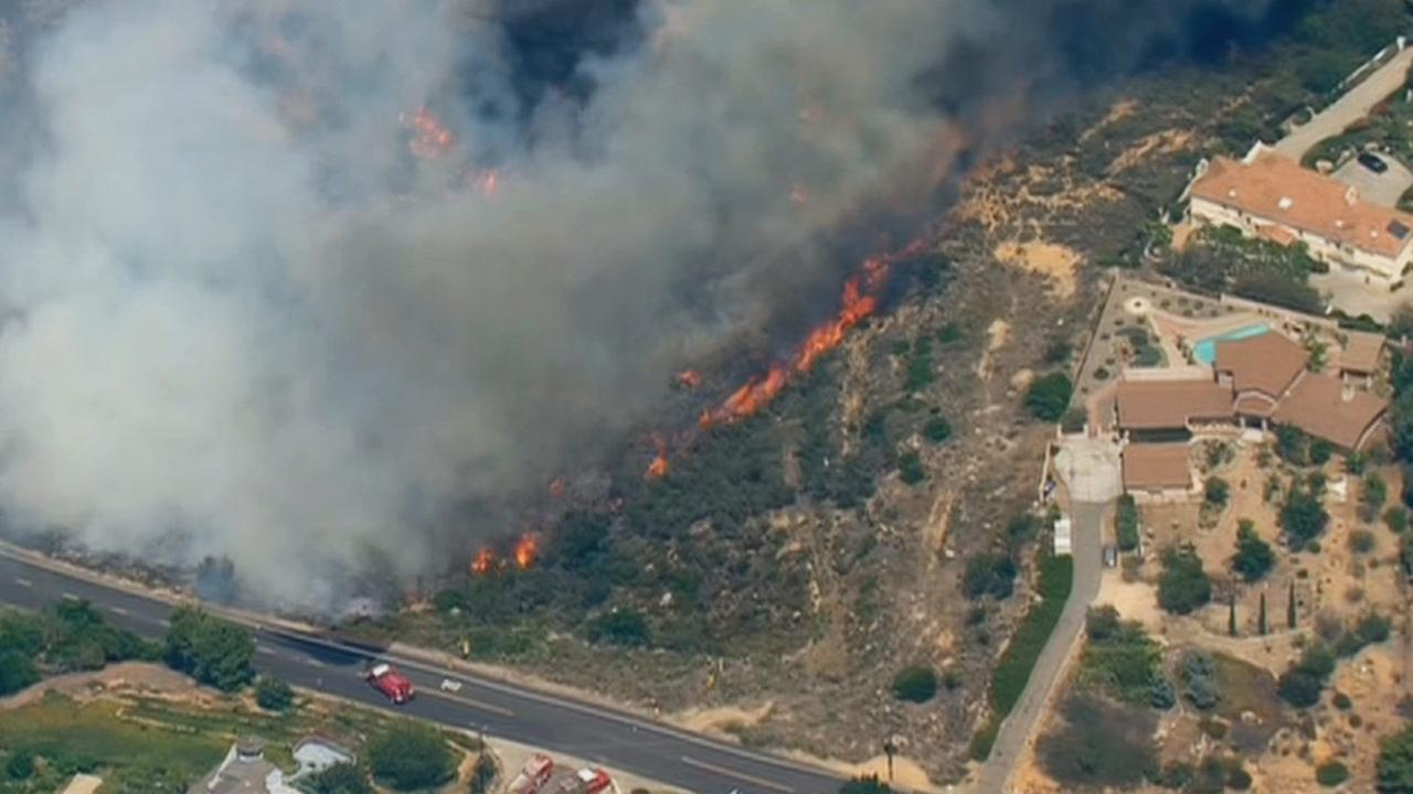 Flames approach homes in San Diego County on Thursday, May 15, 2014.