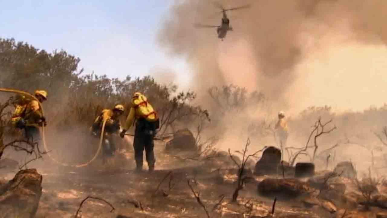 A water-dropping helicopter targets a patch of brush fire in San Diego County as firefighters mop up flames Saturday, May 17, 2014.
