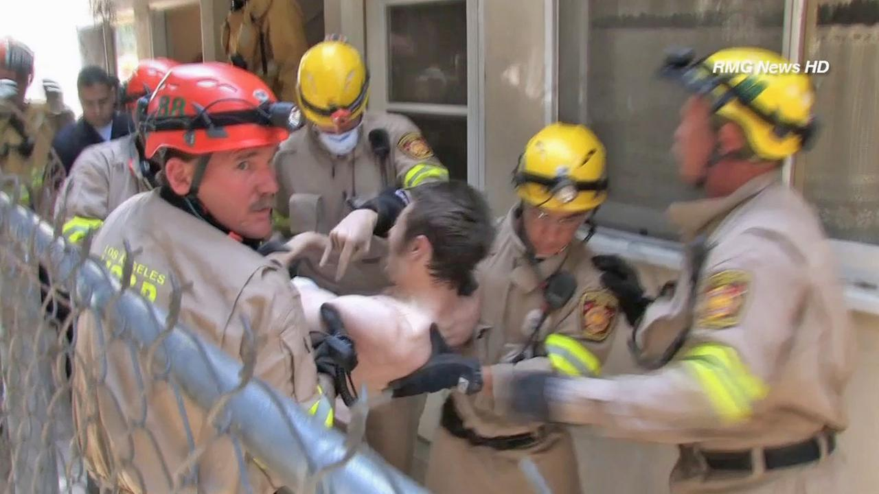 Rescuers remove a naked man who went underneath a crawl space at a Sherman Oaks apartment building on Sunday, May 18, 2014.