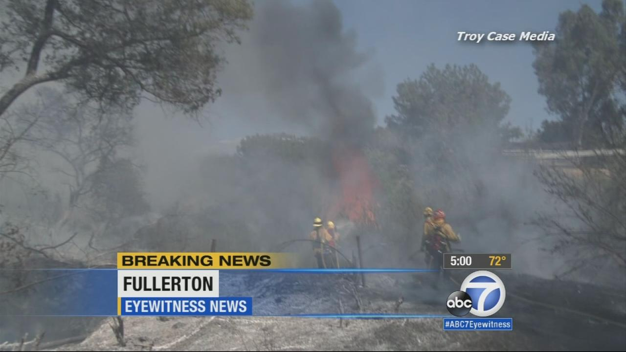 Fullerton and Orange County Fire Authority firefighters battle a vegetation fire near the Brea Dam in Fullerton Saturday, April 18, 2015.