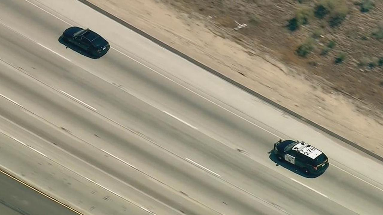 California Highway Patrol officers pursue a suspect in a stolen black BMW on the northbound 15 Freeway in San Bernardino County.
