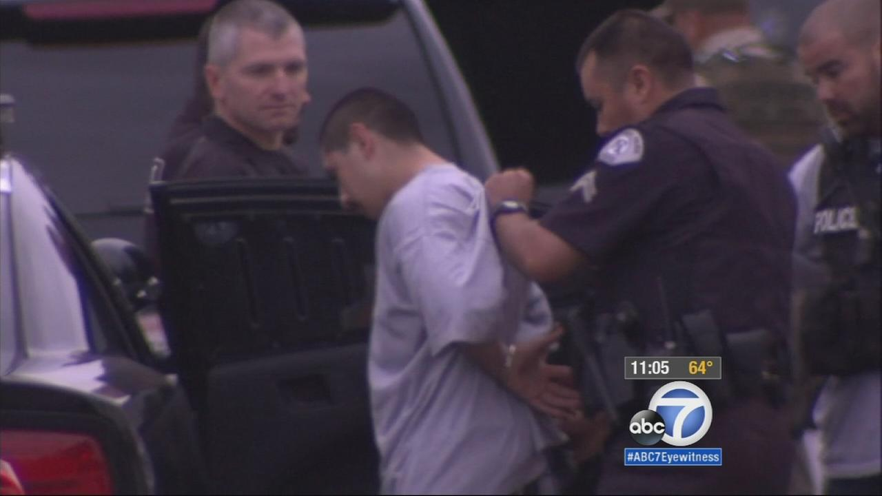 A law enforcement official detains a man for questioning regarding a fatal shooting in Baldwin Park.