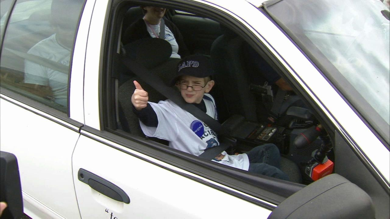 He flashes a thumbs up when he gets settled in the police cruiser.