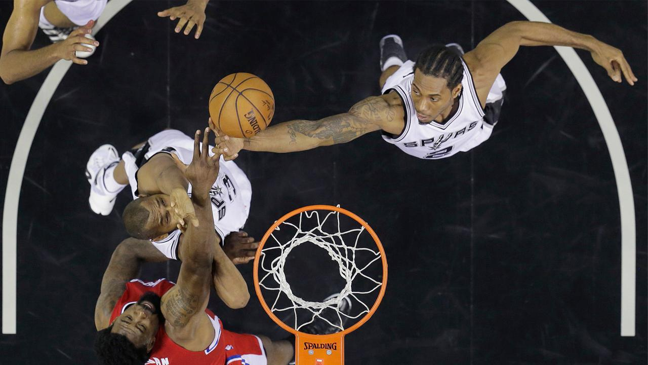 Los Angeles Clippers DeAndre Jordan, bottom left, goes up for a rebound along with San Antonio Spurs Boris Diaw in Game 3 of the NBA basketball playoff series, April 24, 2015.