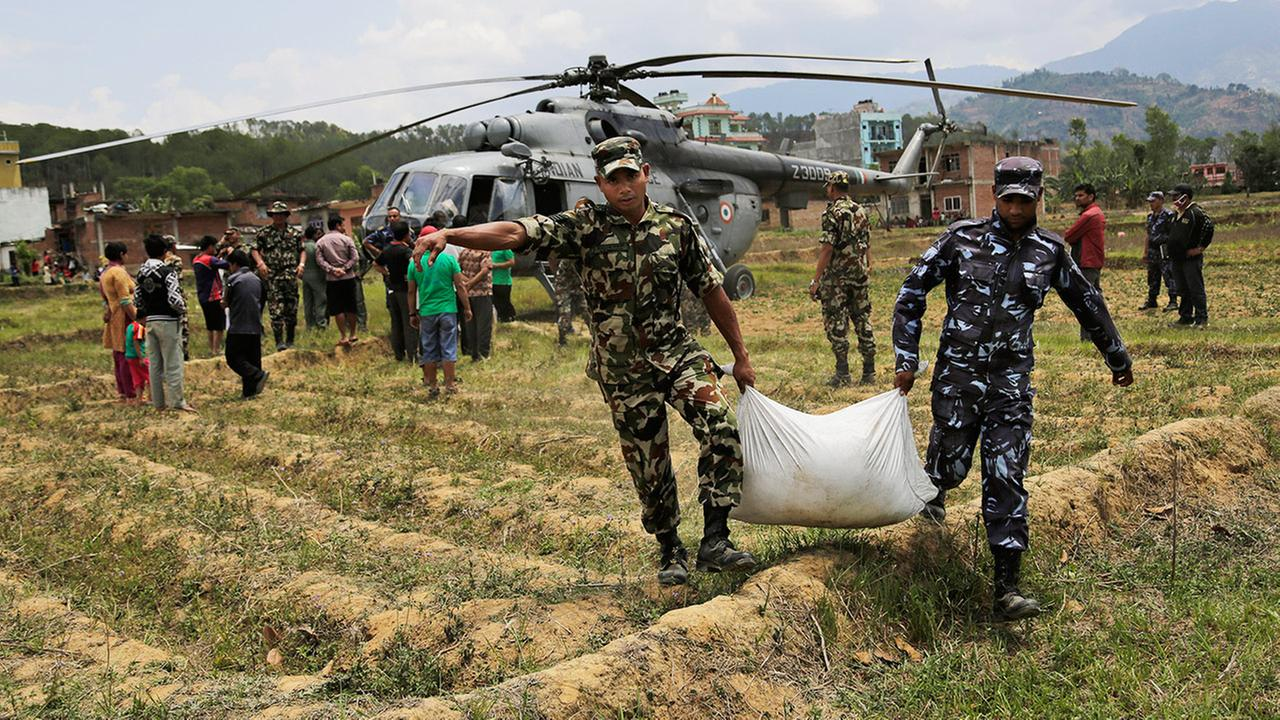 Nepalese soldiers unload relief material brought in an Indian air force helicopter for victims of Saturdays earthquake at Trishuli Bazar in Nepal, Monday, April 27, 2015.