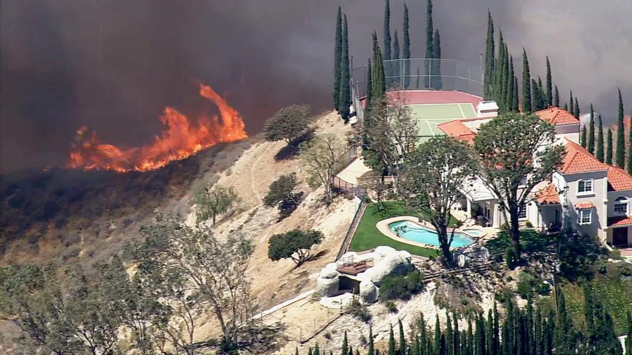 A wind-driven brush fire burns near structures in the 12300 block of Highwater Road in the Knollwood section of Granada Hills on Monday, April 27, 2015.