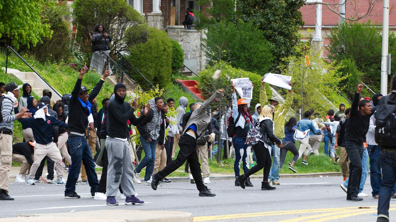Demonstrators throw rocks to the police, after the funeral of Freddie Gray, Monday, April 27, 2015, at New Shiloh Baptist Church in Baltimore.