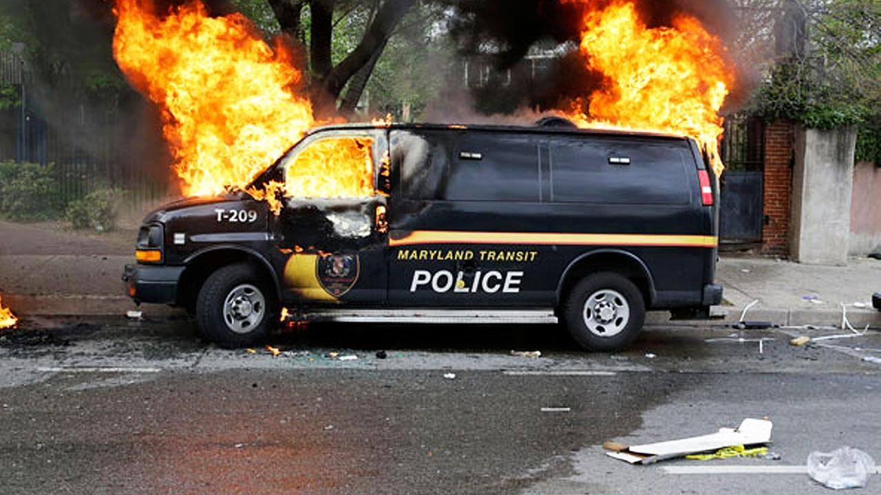 A police vehicle burns, Monday, April 27, 2015, during unrest following the funeral of Freddie Gray in Baltimore.