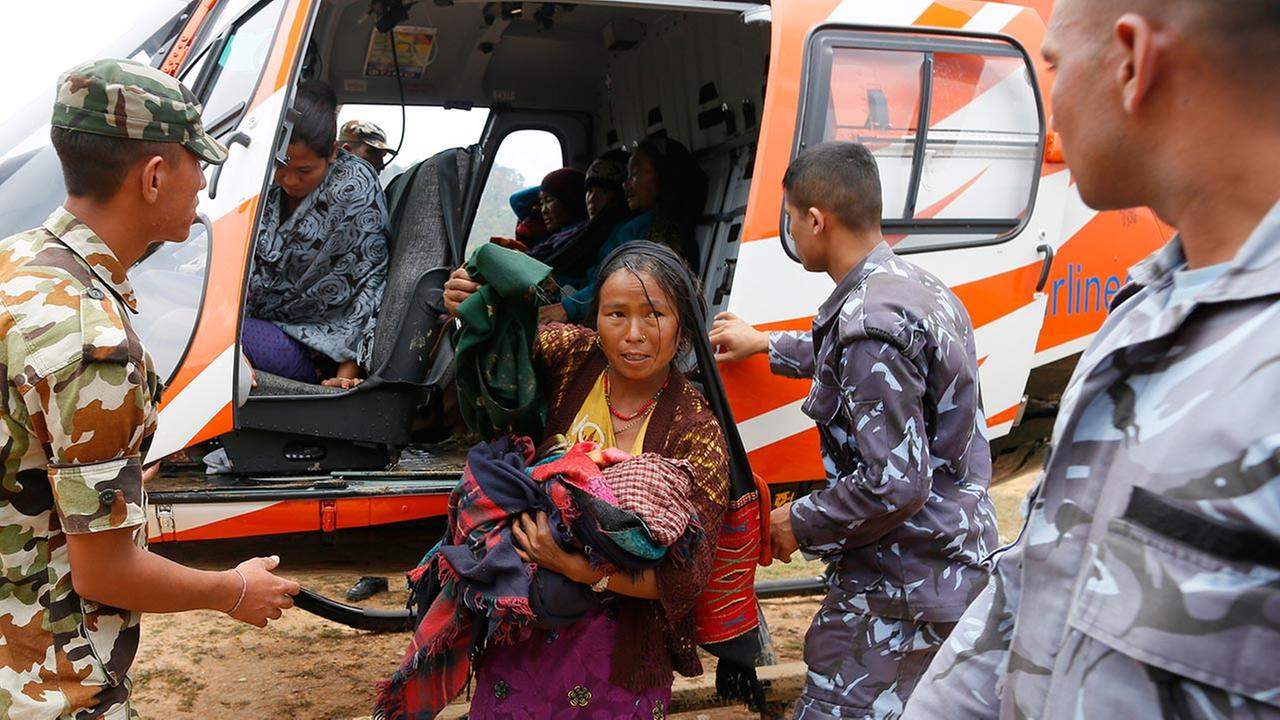 A mother injured from Saturdays quake, carries her baby as she arrives by helicopter from the heavily-damaged Ranachour village at a landing zone in Gorkha, Nepal April 28, 2015.