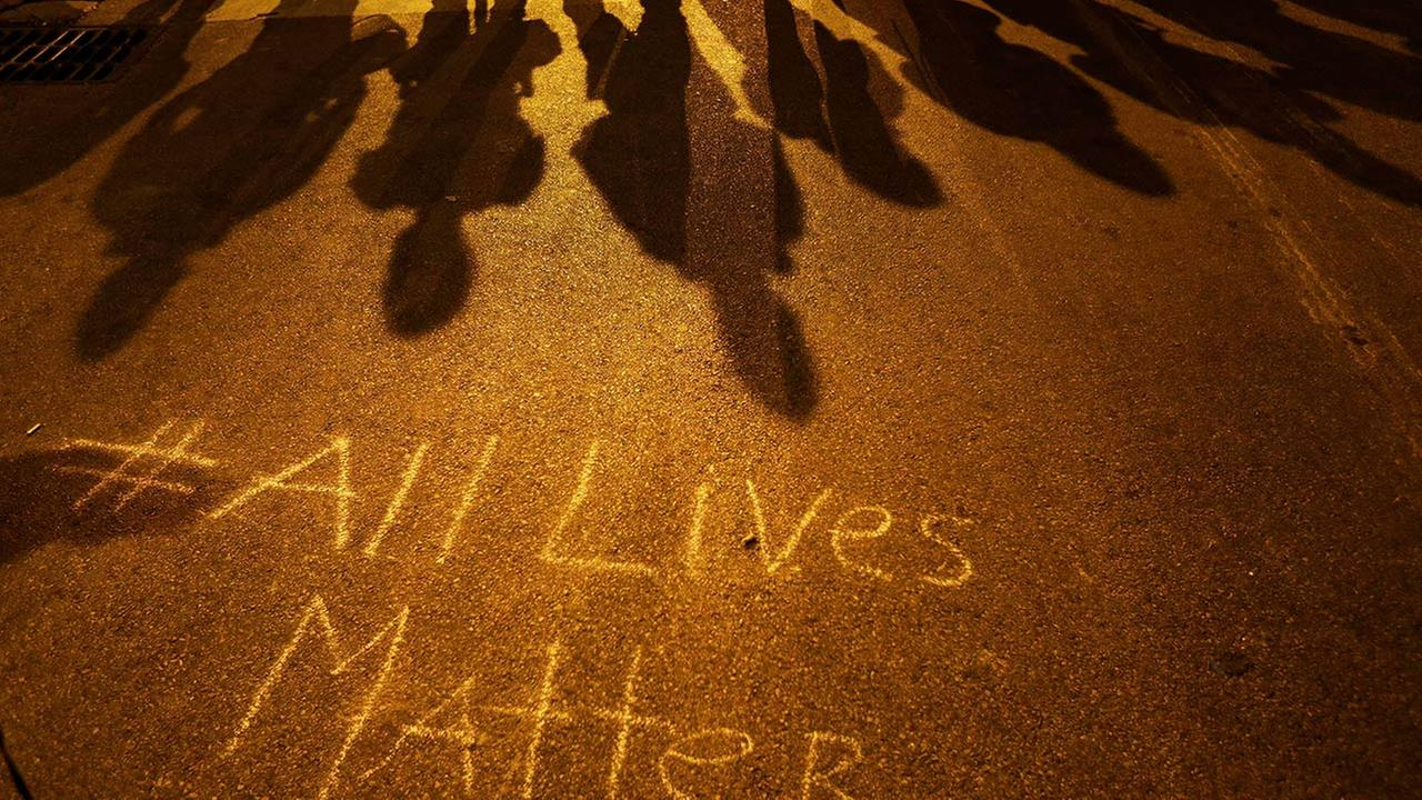A message reading All Lives Matter is written on the pavement as police in riot gear cast shadows while standing in line ahead of a curfew Friday, May 1, 2015, in Baltimore.