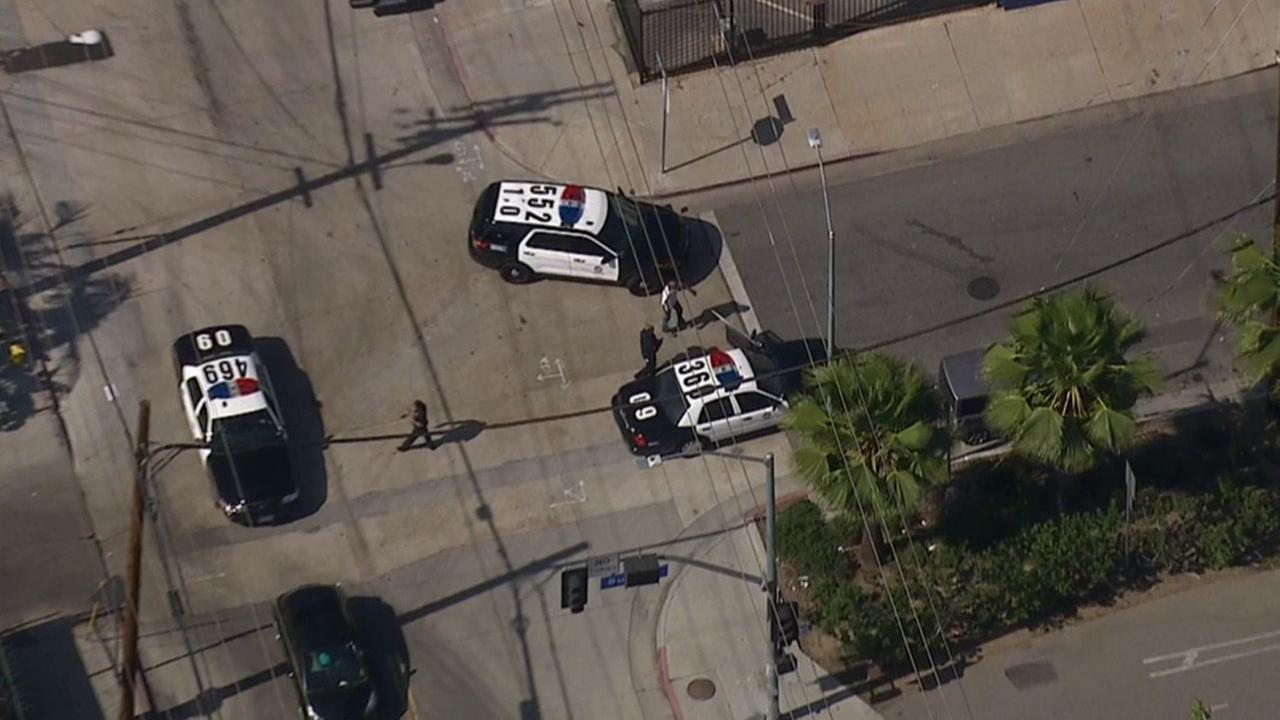 Los Angeles police officers assist state parole officers in the search for a suspect near Tyrone Avenue and Erwin Street in Van Nuys Monday, May 4, 2015.