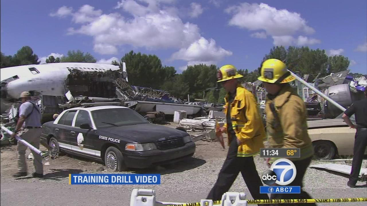 Two first responders walk through a fake plane wreckage at Universal Studios during a statewide drill on Tuesday, May 20, 2014.
