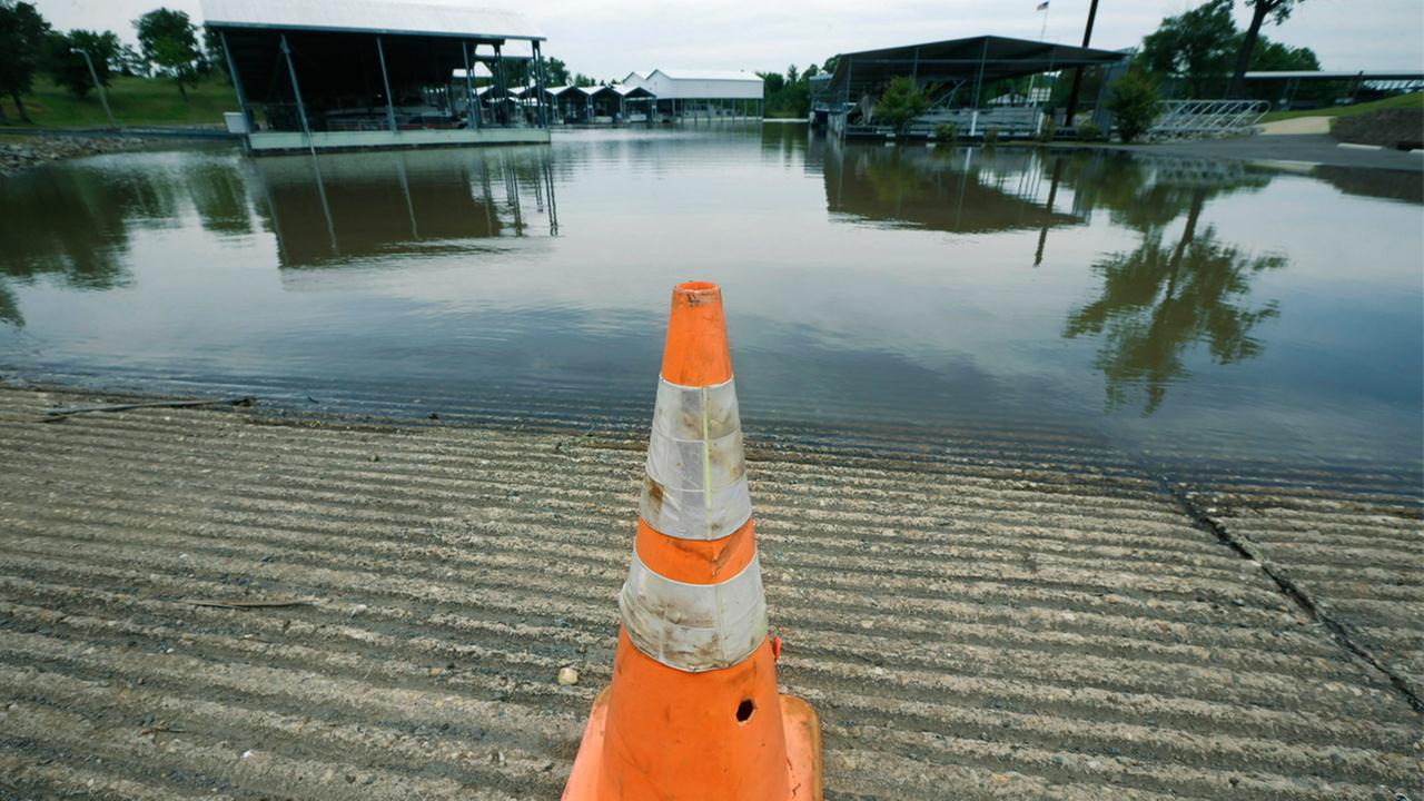A traffic cone blocks entry to a boat ramp and flooded parking lot at Little Rock Yacht Club Marina near Little Rock, Ark., Friday, May 22, 2015.