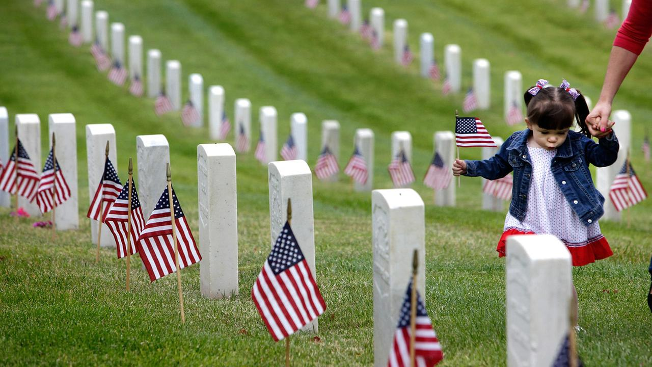 Madelyn Andrews, of Woodland Hills, Calif., walks past military graves while placing flags at headstones in remembrance of Memorial Day, Monday, May 25, 2015.