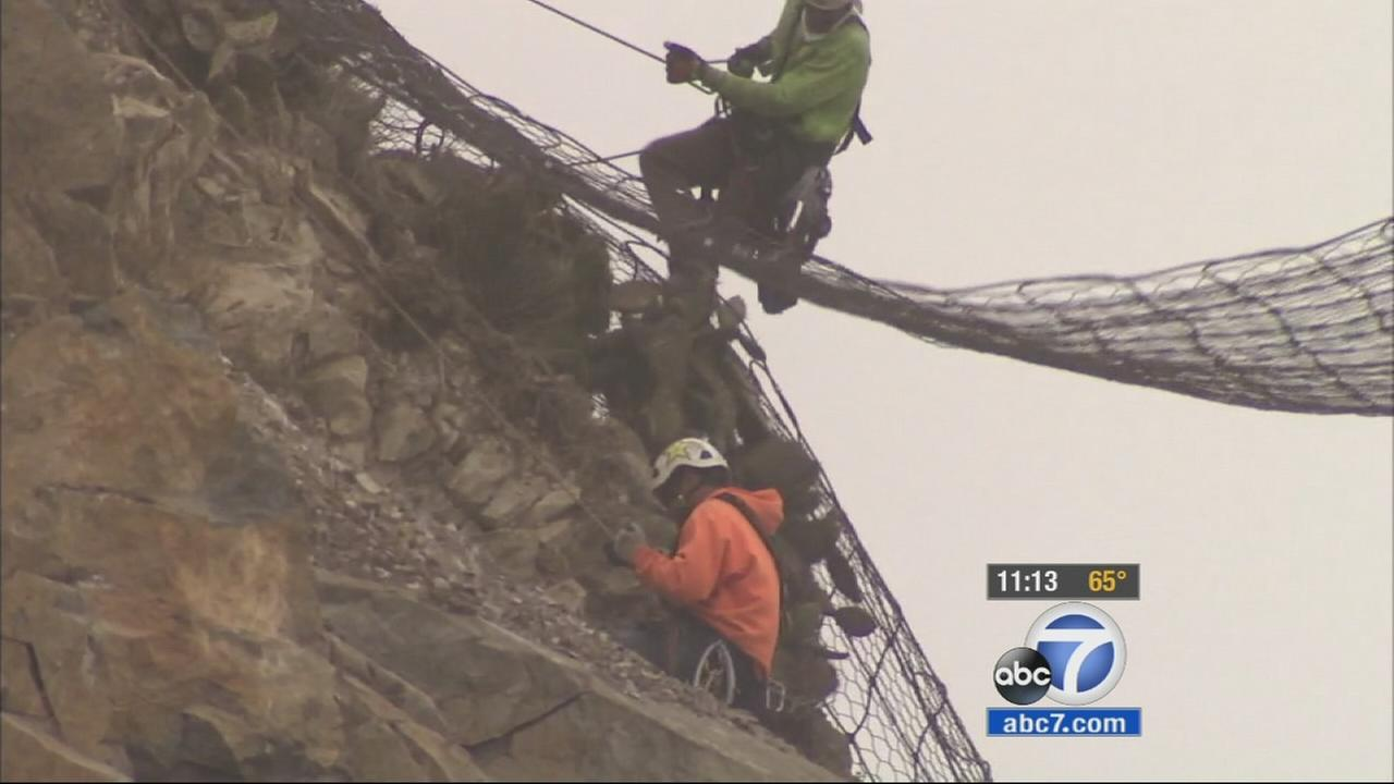 Rock climbers secure nets across the rock face in Malibu along Pacific Coast Highway on Wednesday, May 27, 2015.