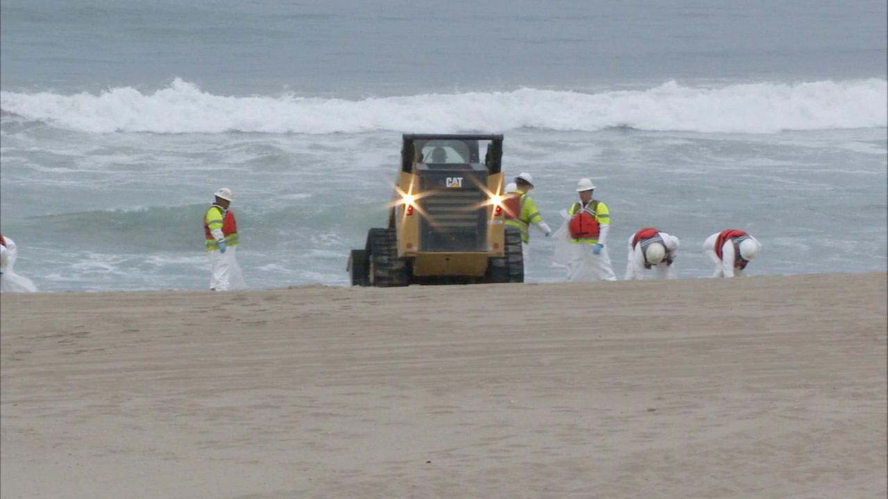Crews clean oily substance from sand along the Manhattan Beach coastline on Thursday, May 28, 2015.
