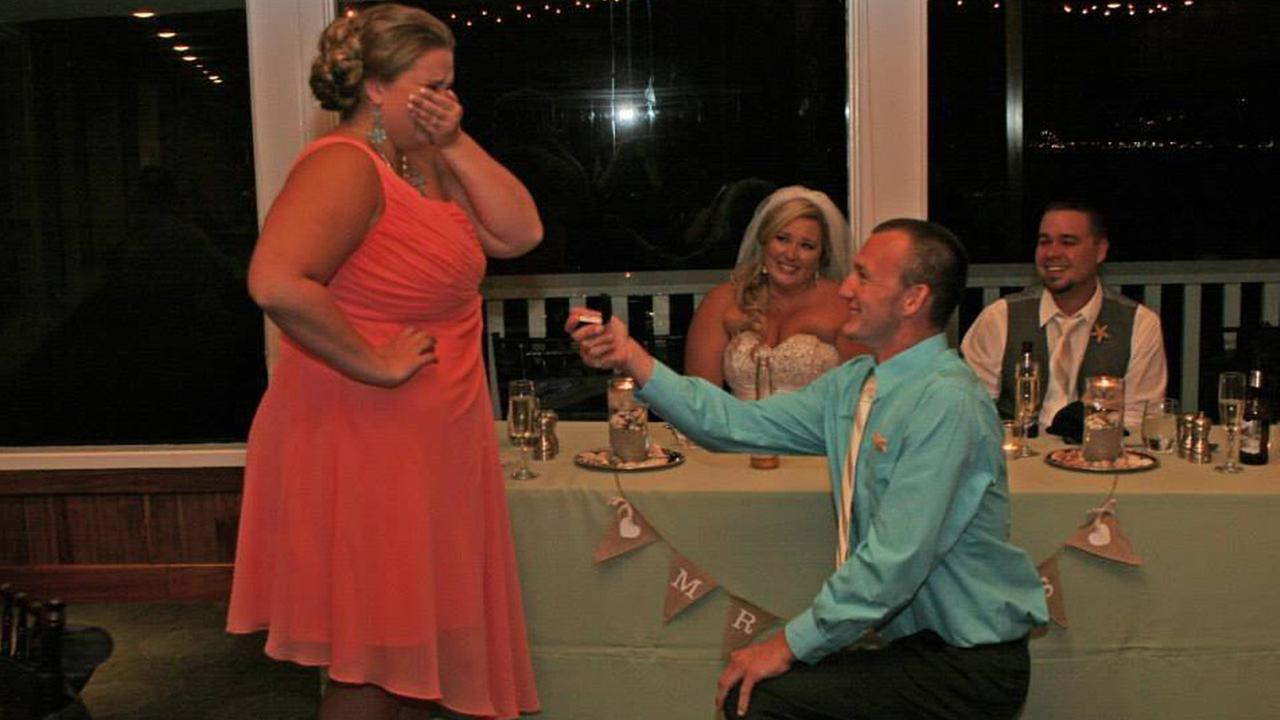 The best man proposes to the maid of honor, named Megan, during another couples wedding reception.