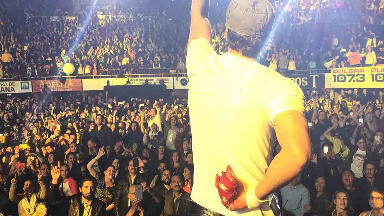 In this photo provided by Francis Ramsden, Enrique Iglesias performs while holding his bloodied and bandaged right hand behind his back during a concert in Tijuana, Mexico on Saturday, May 30, 2015.