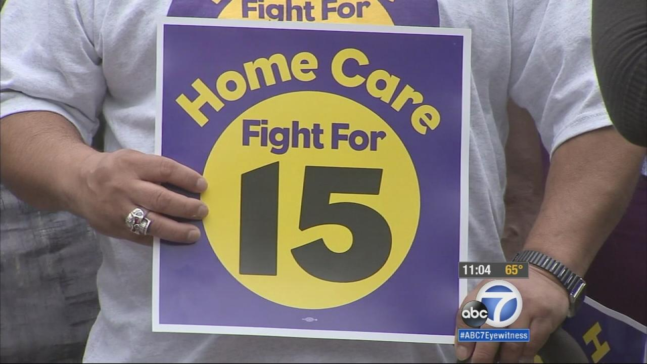 A worker holds up a sign in support of raising the minimum wage in Los Angeles to $15 an hour.