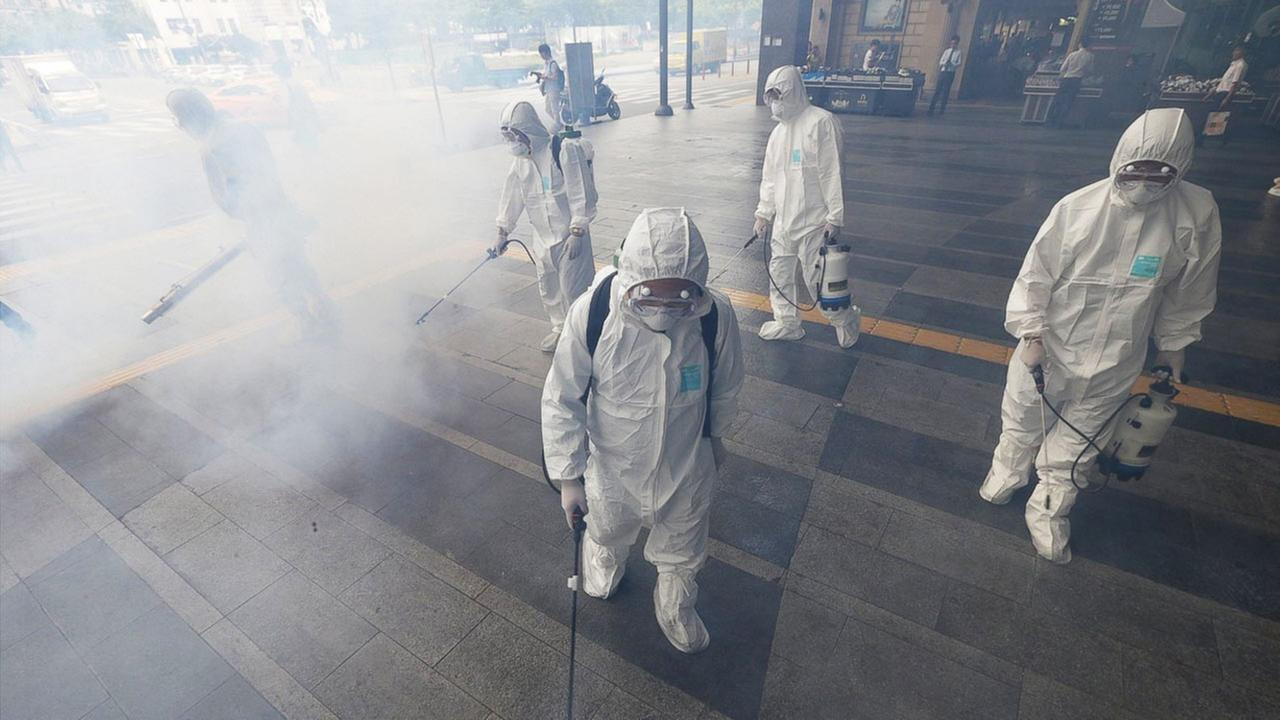 Workers wearing protective gears spray antiseptic solution as a precaution against the spread of MERS virus outside Wangsimni Subway Station in Seoul, South Korea, June 11, 2015.