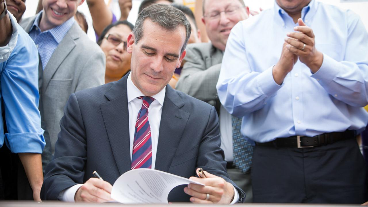 Mayor Eric Garcetti signs the ordinance which will increase minimum wage to $15 an hour by 2020 on Saturday, June 13, 2015 at Martin Luther King Jr Park.