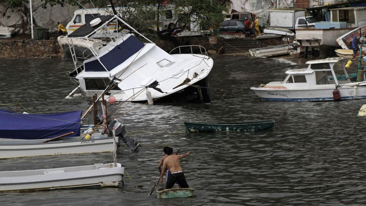 Two men paddle on a small boat towards a yatch that was damaged by winds and rains from hurricane Carlos in the Pacific resort city of Acapulco, Mexico, Sunday, June 14, 2015.