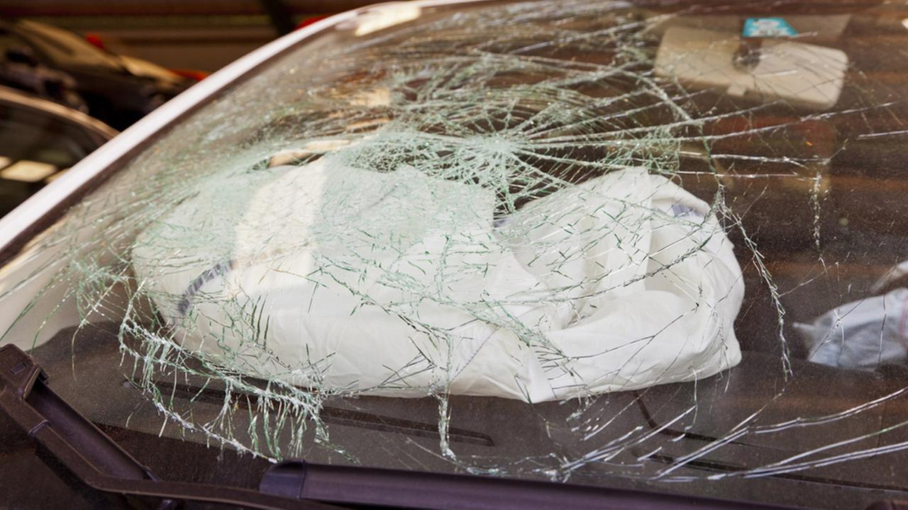 A smashed windshield and deflated air bag are shown in an undated photo.