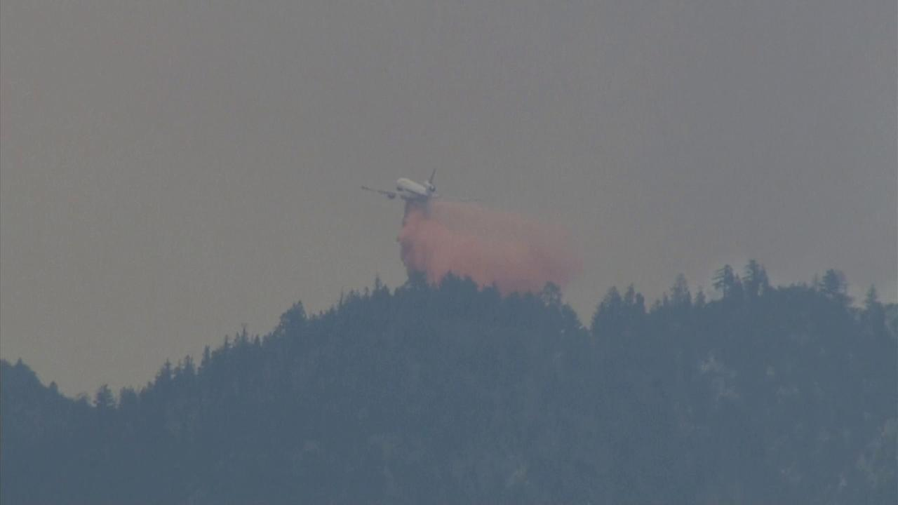 A firefighting aircraft drops water and fire retardant on the Lake Fire.