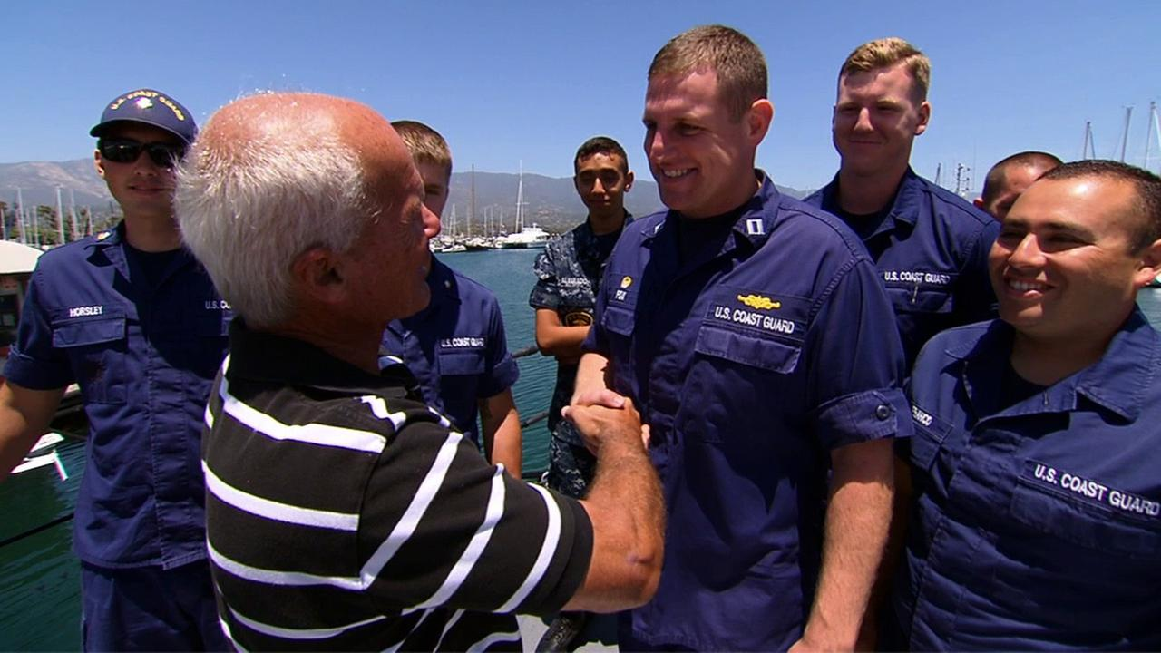 Ron Webber shakes the hand of a crew member of the U.S. Coast Guard who rescued him after 14 hours at sea.