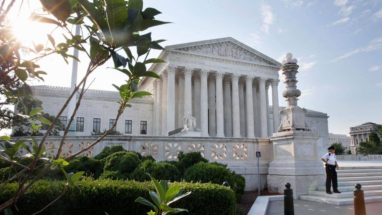 Security guards stand outside the Supreme Court in Washington, Thursday June 25, 2015.