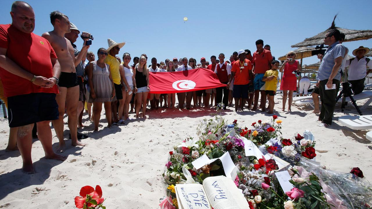 People, some displaying a Tunisian flag, stand in silence next to flowers during a gathering at the scene of the attack in Sousse, Tunisia, Sunday, June 28, 2015.