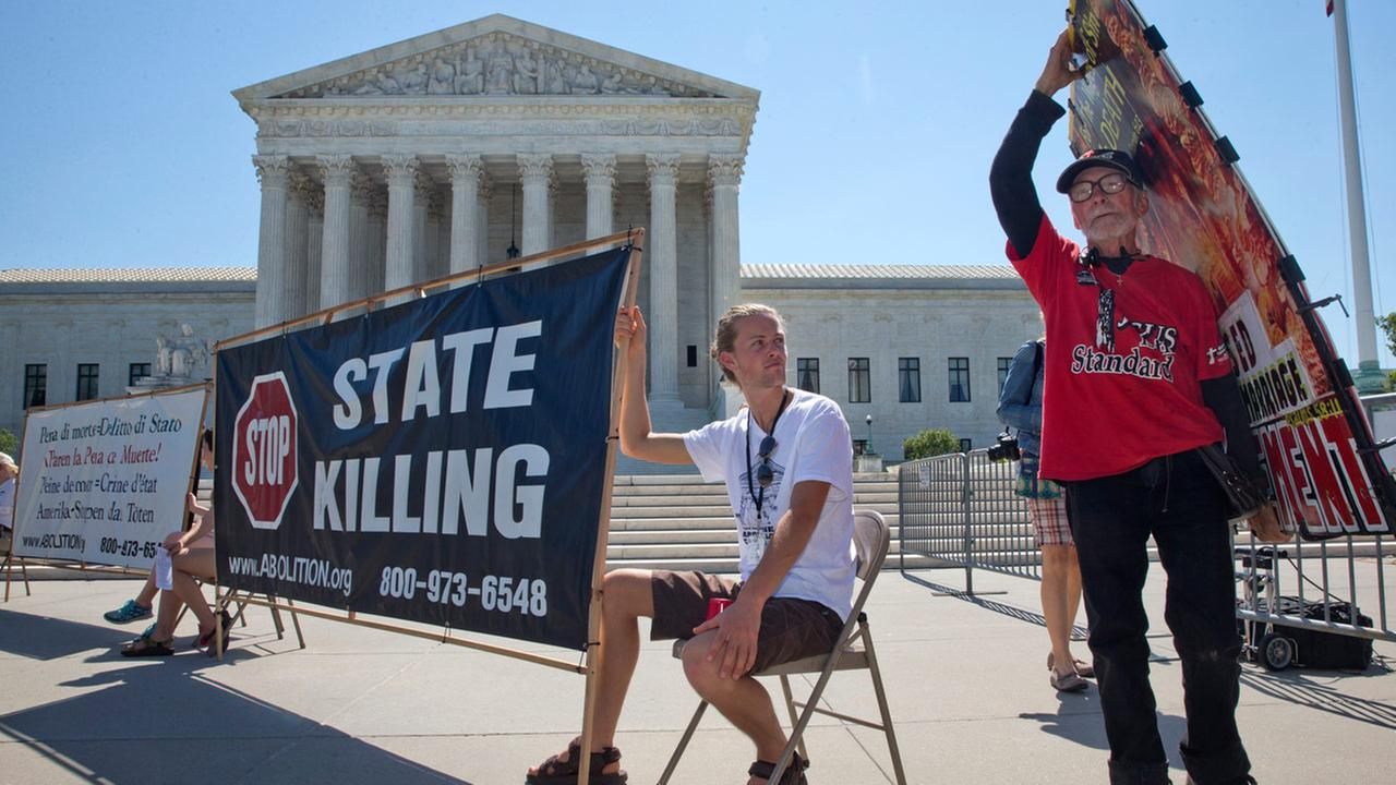 Jack Leason, 19, of Wellington, New Zealand, left, attends a protest against the death penalty outside of the Supreme Court Monday June 29, 2015, in Washington.