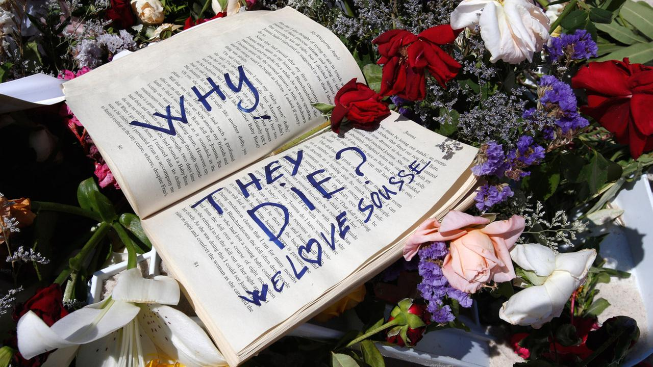 In this Sunday, June 28, 2015 file photo, a book and flowers lay at the scene of the attack in Sousse, Tunisia.