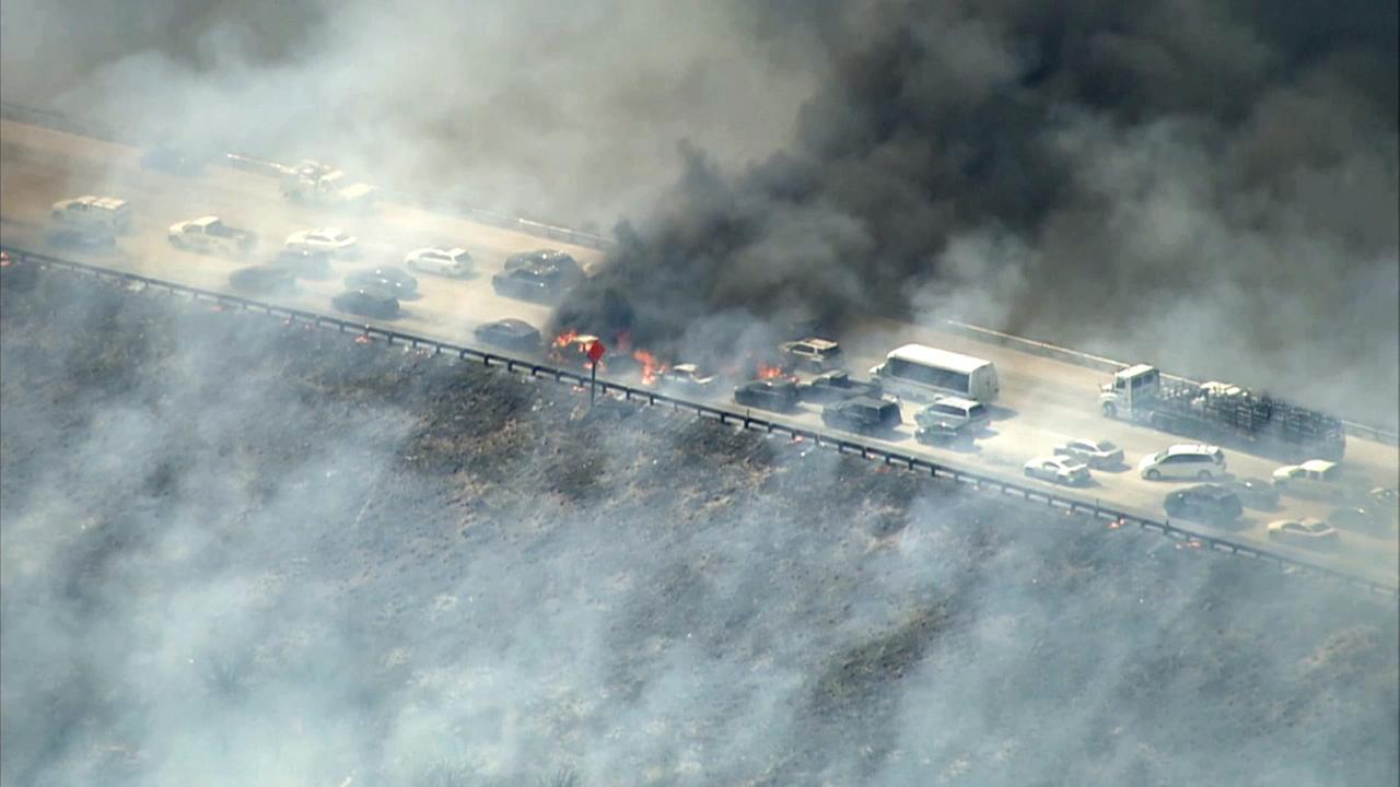 Several cars caught on fire after a brush fire shut down the 15 Freeway at Oak Hill Road in the Cajon Pass on Friday, July 17, 2015.